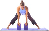 yoga beginner standing wide leg forward fold with blocks
